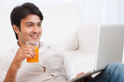 Man using a laptop with a glass of juice